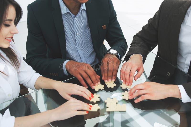 折叠难题的成功的企业队坐在书桌后 图库摄影