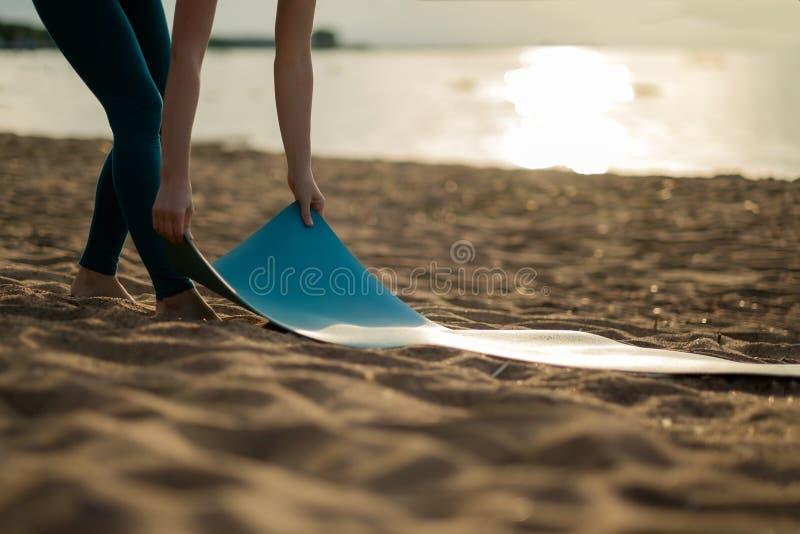 折叠绿色瑜伽或健身席子的可爱的少妇在解决以后在海滩 库存图片