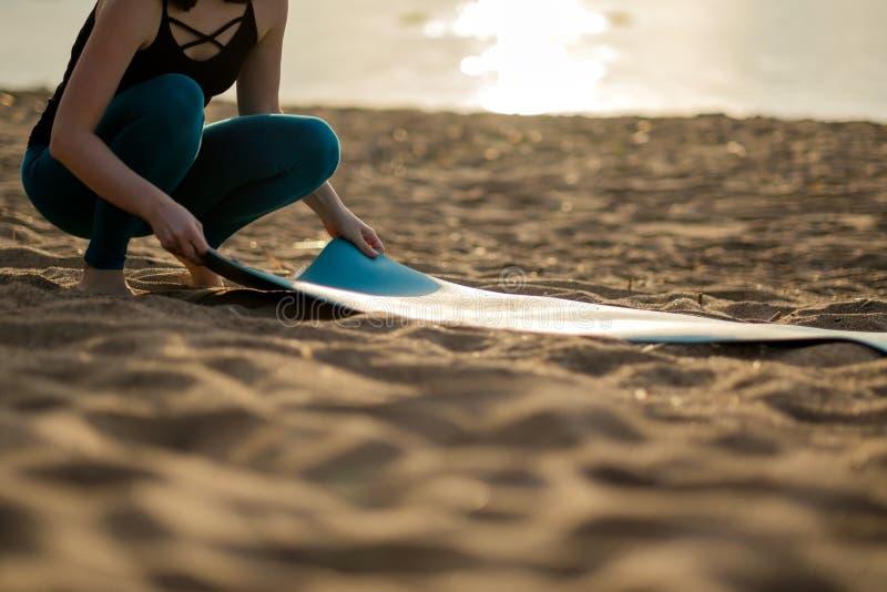 折叠绿色瑜伽或健身席子的可爱的少妇在解决以后在海滩 免版税图库摄影