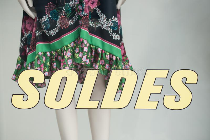 折扣标志- SOLDES -用法语,销售的诋毁在窗口的在法国时尚商店 库存照片