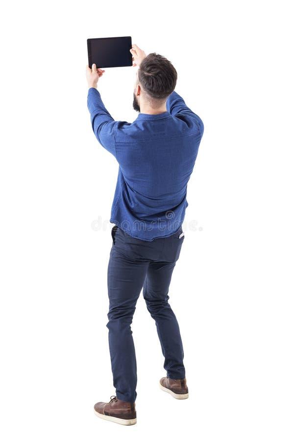 抚养拍与片剂的后面观点的典雅的英俊的商人selfie照片 免版税图库摄影