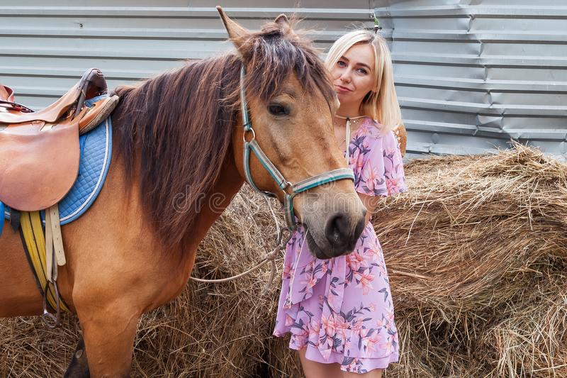 抚摸一匹棕色马的头的少女在干草堆附近吃干草在一个夏天晴天的步行前 免版税库存图片