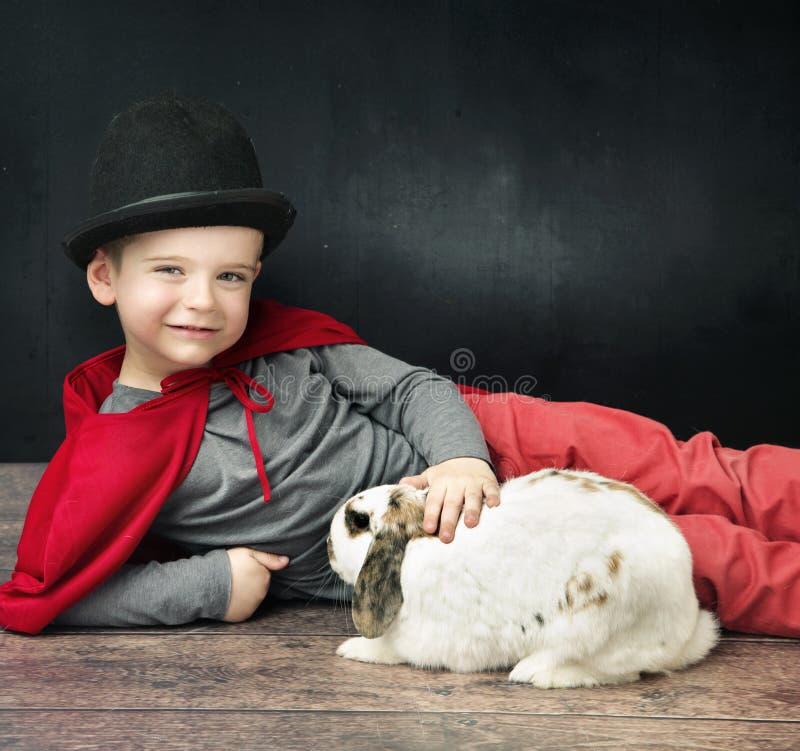 抚摸兔宝宝的小魔术师男孩 免版税图库摄影