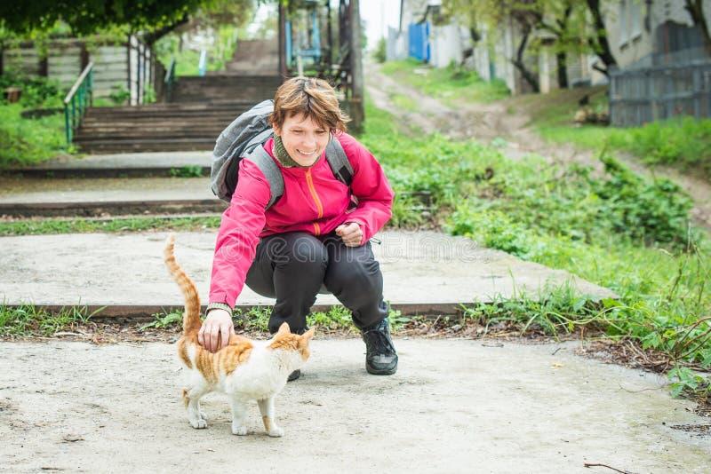 抚摸在街道上的微笑的妇女一只发出愉快的声音的猫 无家可归的动物 免版税库存图片