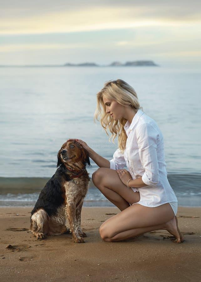 抚摸她心爱的狗的白肤金发的小姐 免版税库存照片