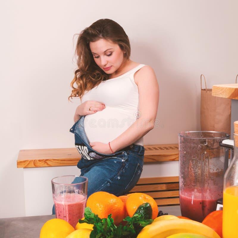 抚摸她的胃用在前景的果子的美丽的孕妇 免版税库存照片