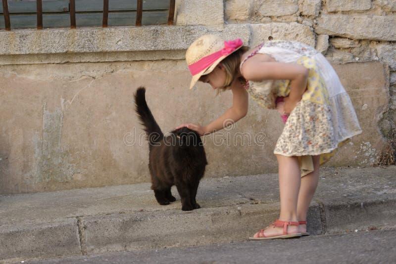 抚摸猫的女孩 免版税库存图片