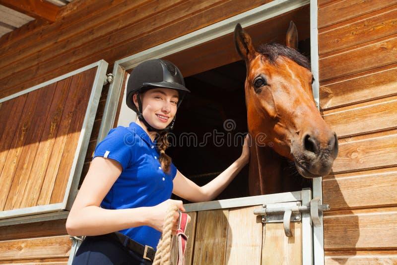 抚摸马的愉快的骑师女孩在马棚 库存图片