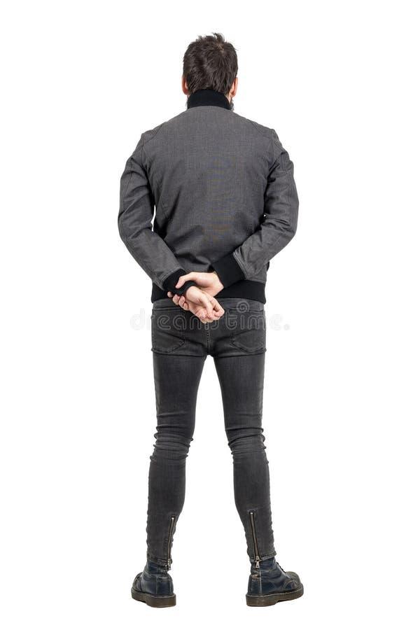 抚养后面观点的紧的看牛仔裤和灰色的夹克的人  库存照片