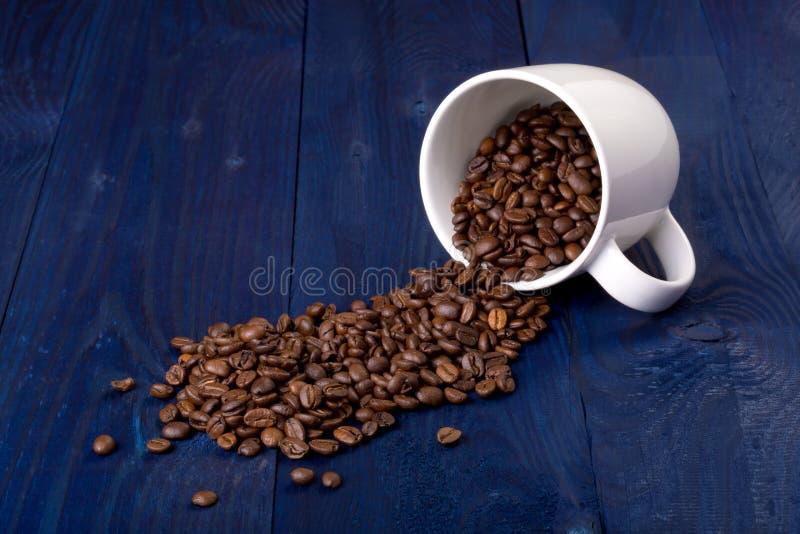 抢劫并且溢出了在蓝色木背景的咖啡豆 图库摄影