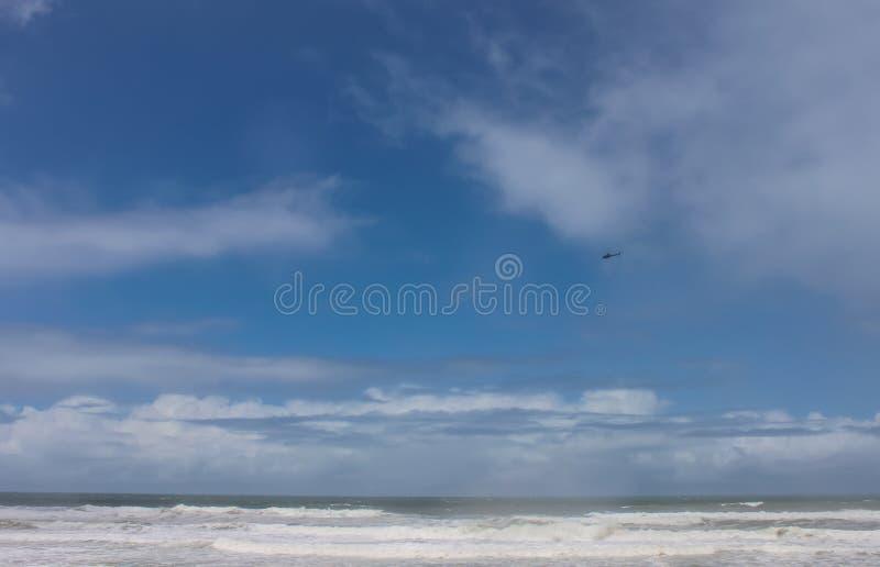 抢救在搜寻麻烦的人的浪潮起伏的狂放的海洋上的直升机飞行 库存图片