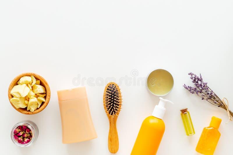 护发的化妆用品用加州希蒙得木,圆筒芯的灯或椰子油 油瓶和片断在白色背景顶视图的复制 库存图片