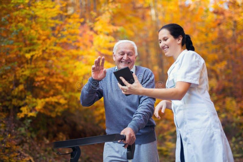 护士和失去能力的资深患者使用数字式片剂的步行者的室外 库存照片