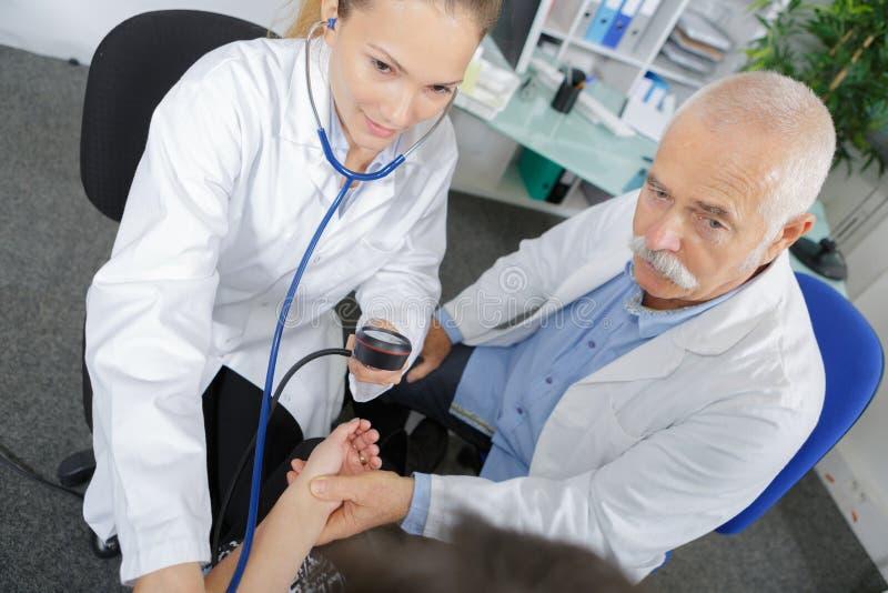护士和资深医生测量的血压妨碍了人 图库摄影