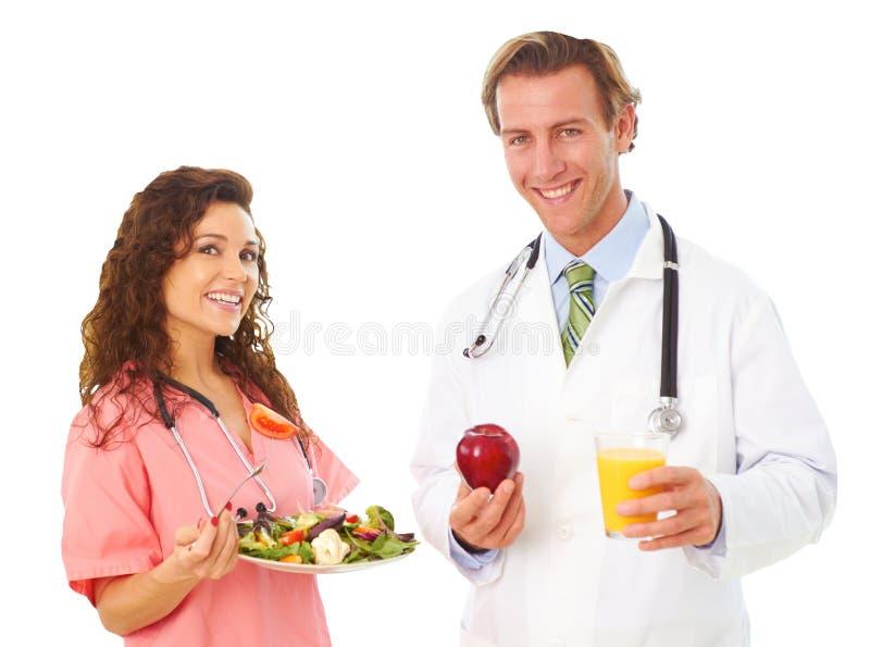 护士和Holding医生健康食品 免版税库存照片