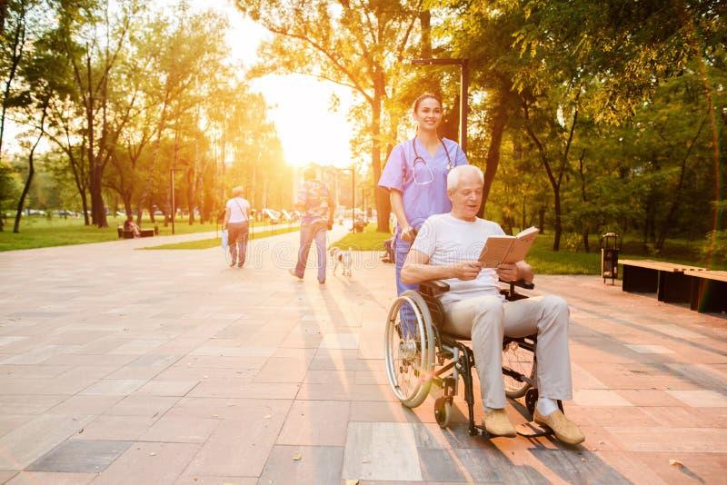 护士在一个老人后站立,在轮椅坐并且读书在日落 图库摄影