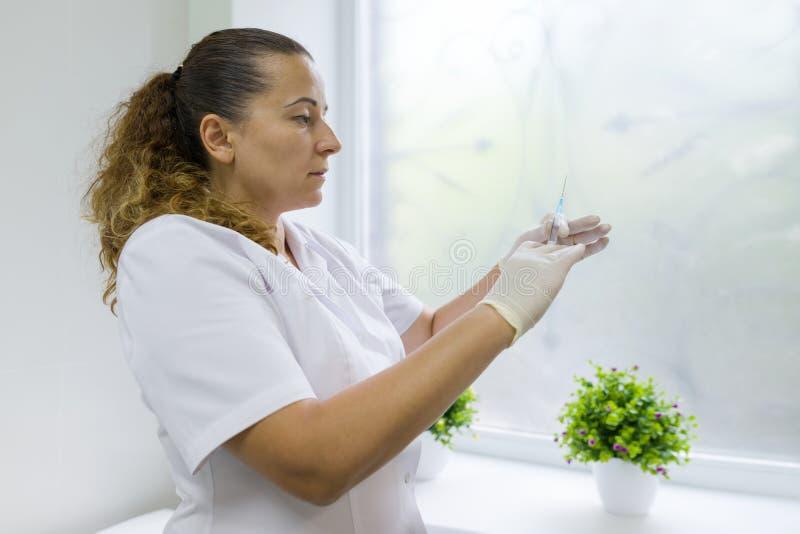 护士在医院拿着一个注射器,为射入做准备,反对窗口 免版税库存照片