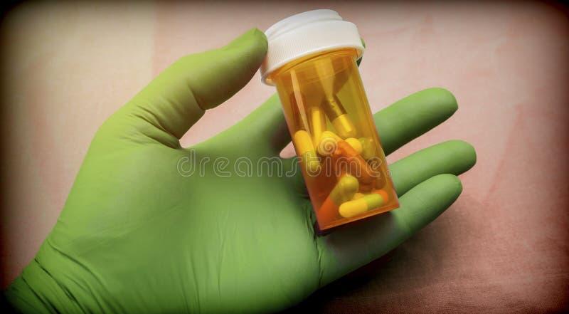 护士在医院支持有左手的胶囊瓶与绿色乳汁手套  免版税库存照片