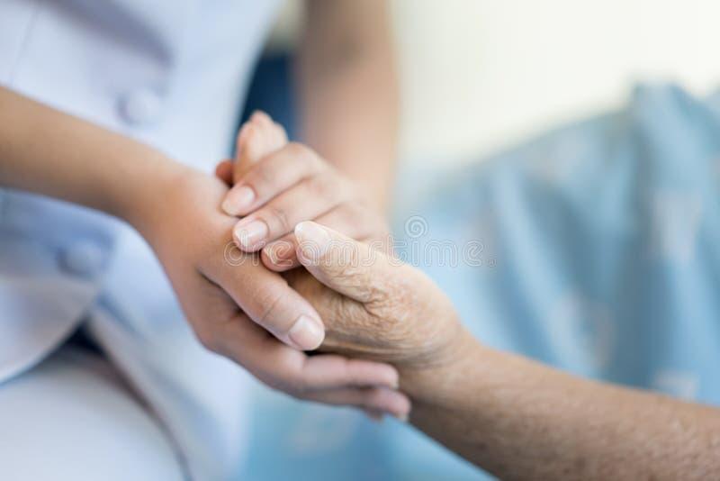 护士坐医院病床在一个老妇人帮手旁边,年长概念的关心 库存图片