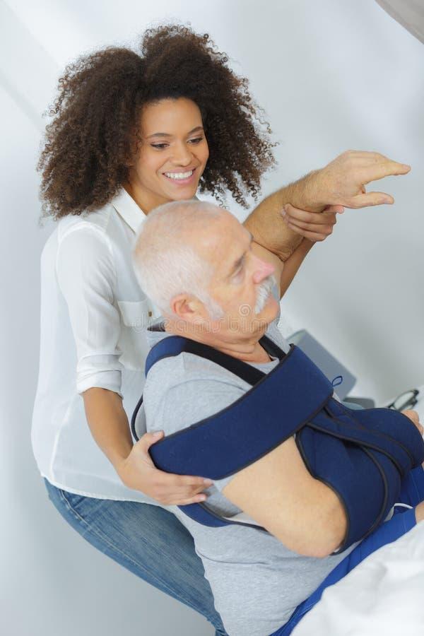 护士帮助的前辈胳膊在家 免版税库存照片