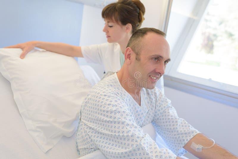 护士帮助的患者在床上在医院 库存图片