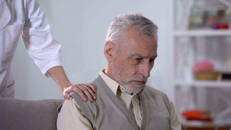 护士支持的沮丧的领抚恤金者在康复中心,仁爱 库存图片