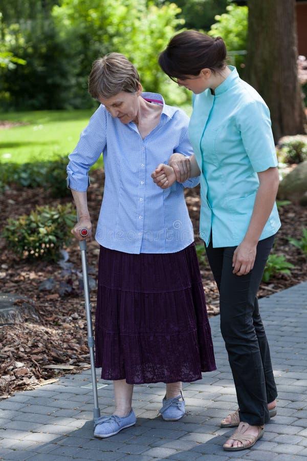 护士散步与老妇人 免版税库存照片