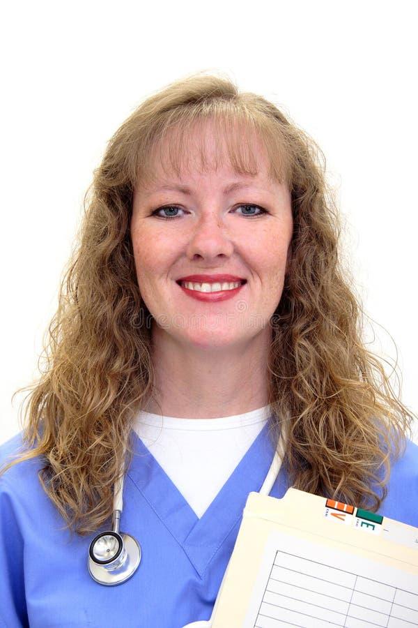 护士洗刷微笑的听诊器 免版税库存照片