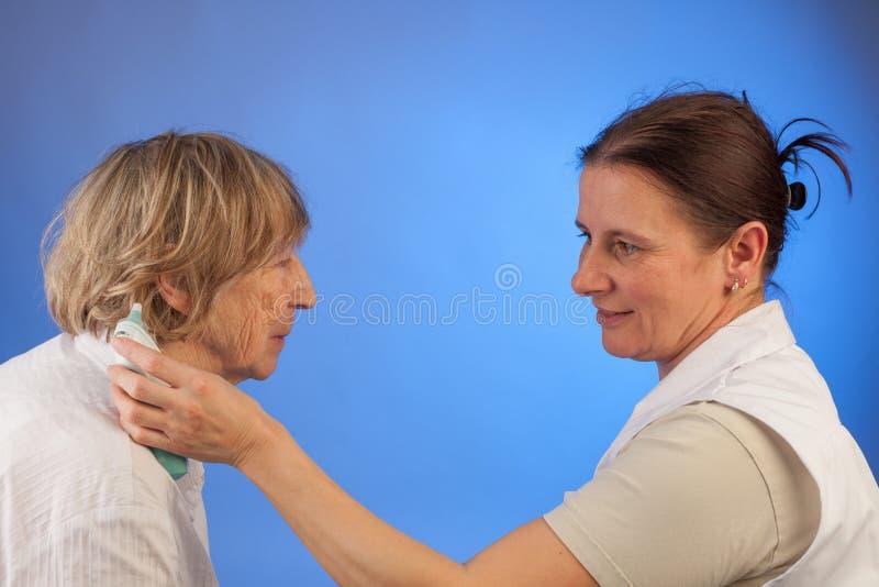 护士测量年长妇女热病  免版税库存照片