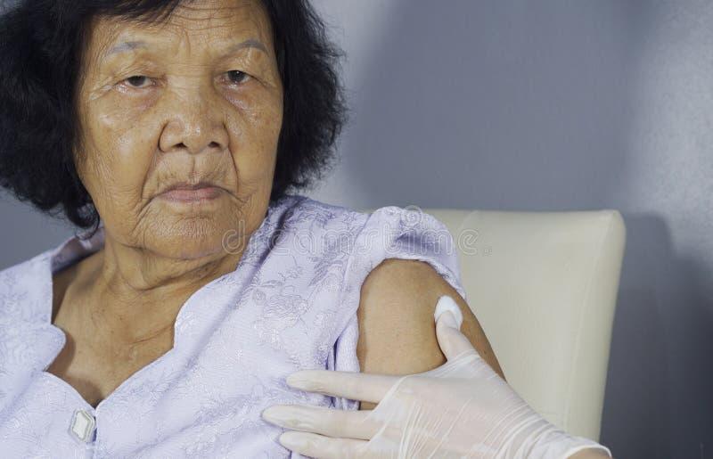 护士清洗皮肤与酒精棉花在妇女得到以后 免版税库存照片