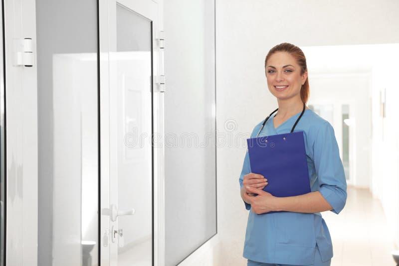 护士画象有剪贴板的在医院走廊 免版税库存照片