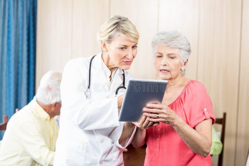 护士谈话与一名资深妇女 库存照片