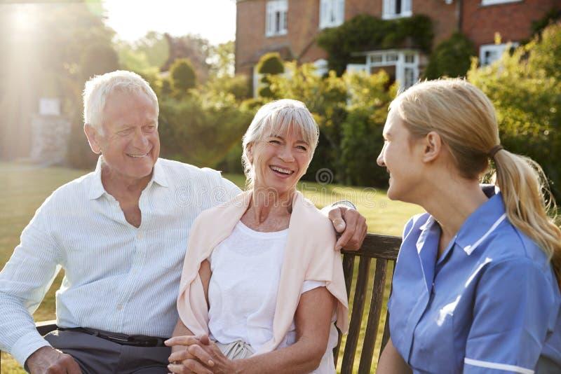 护士谈话与资深夫妇在家庭看护家 免版税库存图片