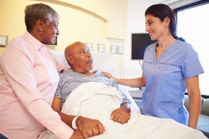 护士谈话与资深夫妇在医房 免版税库存图片