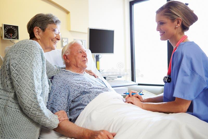 护士谈话与资深夫妇在医房 库存图片