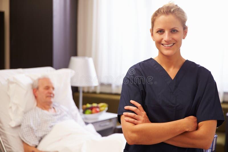 护士画象有资深男性患者的在医院病床上 免版税库存图片