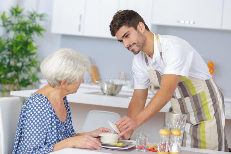 护工对资深妇女的服务午餐 库存图片