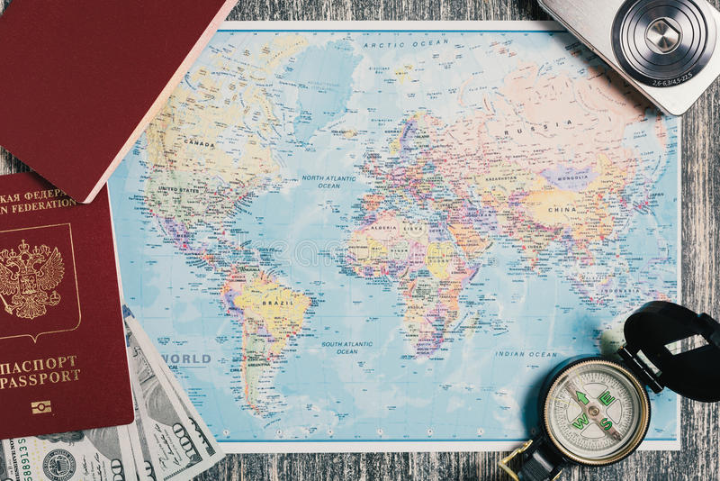 护照、金钱、指南针和照相机在地图 库存照片