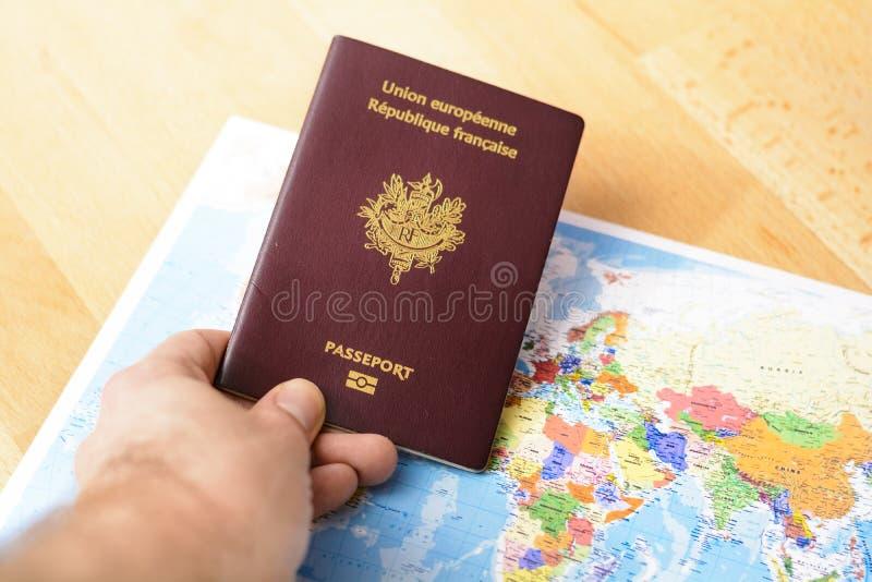 护照在手中与在桌上的世界地图 免版税库存照片