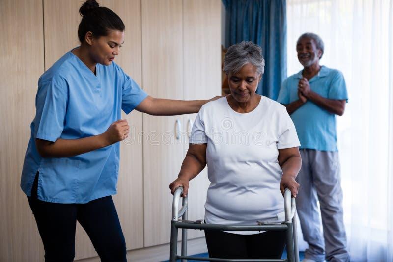 护理协助走的资深妇女与步行者 免版税库存照片