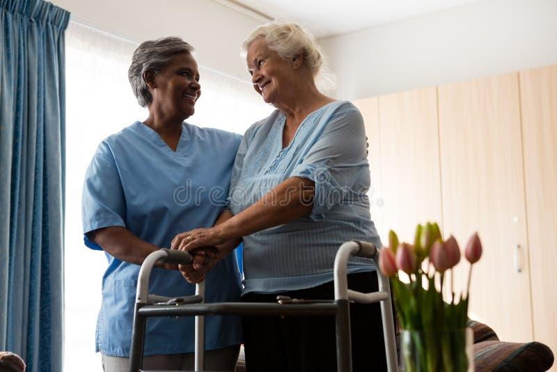 护理协助走的资深患者与步行者 免版税库存照片