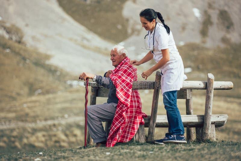 护理帮助的年长老人走在frash空气 免版税库存照片