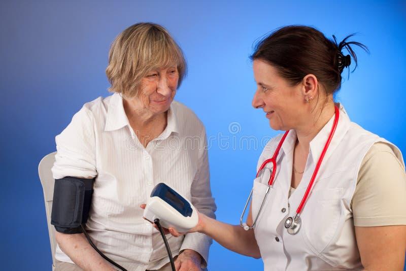 护理措施一名年长妇女的血液presssure 免版税库存照片