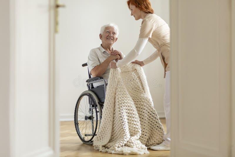 护理照顾一个轮椅的愉快的年长人在他的ho 免版税库存照片
