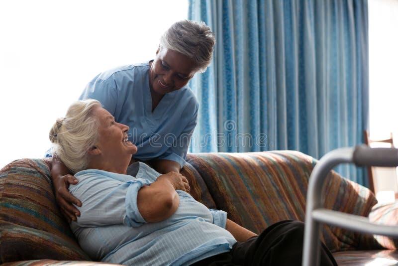 护理谈话与女性患者坐沙发 免版税库存图片