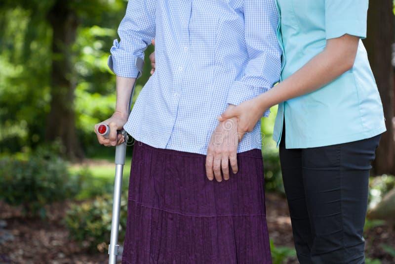护理走与有拐杖的一名女性患者 图库摄影