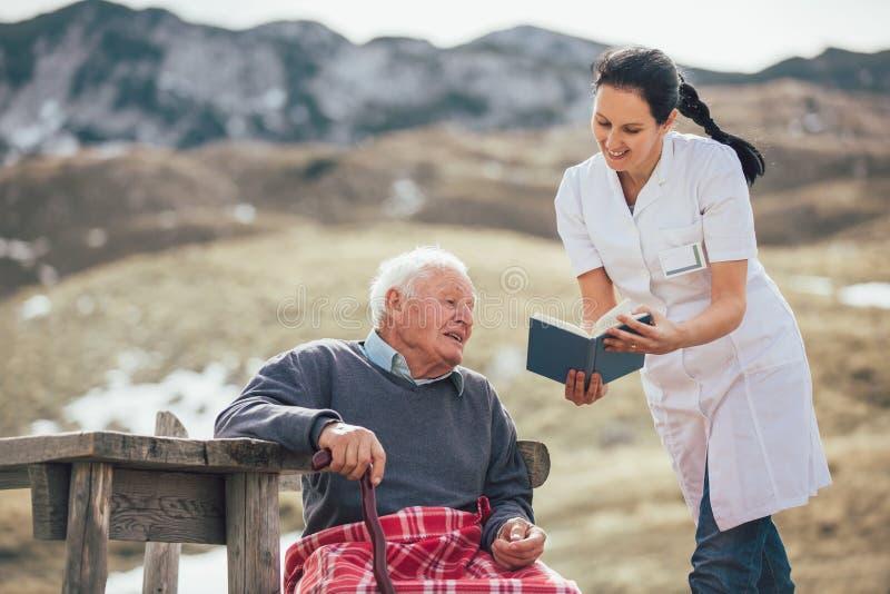 护理阅读书给灰色室外头发的老人 图库摄影