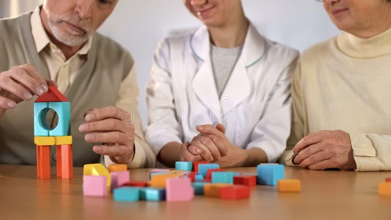 护理颜色木立方体支持的病的男性制造的房子,修复 免版税图库摄影