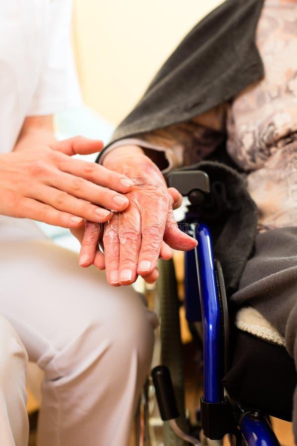 护理高级年轻人的女性家庭护士 免版税库存照片