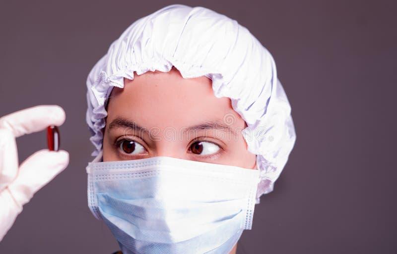 护理阻止照相机的,灰色背景的佩带的鼓胀盖帽和面部面具棕色药片胶囊 图库摄影